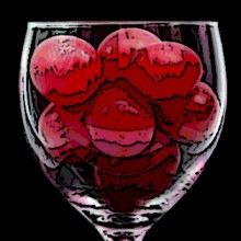 Red grapes in wine glass on black background