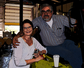 Sue McNerney gets welcome news from Napa Barrel Care's Jorge Vargas atop his forklift.